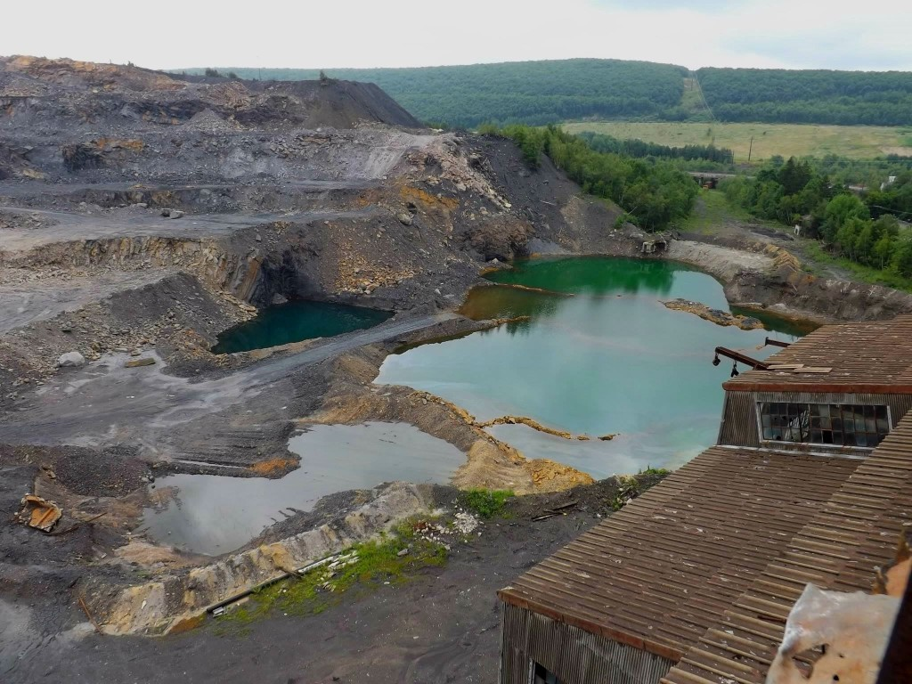 These pools of colored water show that this mining company has hit the mine pool. Blue water indicates mine water that has not been oxidized yet. Orange water indicates oxygenated water with iron hydroxide dropping out to the bottom of the pool. In the background of both photos, heavily forested areas can be seen. Before mining, these areas of black waste and orange water were also heavily forested and home to diverse wildlife.