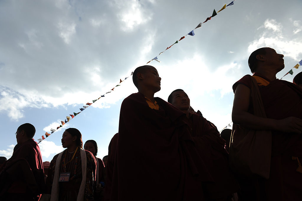 "Indian Buddhist monks and nuns attend a special prayer session 'Avalokesteshvara Initiation' with Tibetan spiritual leader the Dalai Lama at Yid-Gha-Choezin in Tawang, in the northwestern corner of Arunachal Pradesh state, on November 10, 2009. The Dalai Lama held a mass audience with tens of thousands of devotees on a ""non-political"" visit to a region near India's border with Tibet that has drawn shrill protests from China. AFP PHOTO/Diptendu DUTTA (Photo credit should read DIPTENDU DUTTA/AFP/Getty Images)"