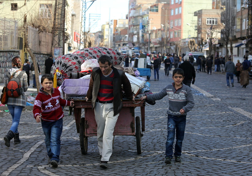 In this photo taken on Wednesday, Feb. 3, 2016, a family leave the Sur district in Diyarbakir, Turkey. The family are among tens of thousands displaced by fighting raging between Turkish security forces and militants in the southeast after a peace process collapsed in the summer. (AP Photo/Murat Bay)